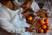 Man Sitting Beside Orange Fruits And Almond On The Floor