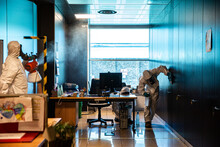 People In PPE Sanitizing An Office