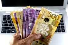 Person Holding 100 And 500 Philippine Peso Banknotes Beside Laptop