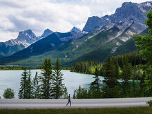 Person Standing On Road Near  Pine Trees And Mountain And Lake