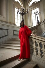 Portrait Of Woman In Red Dress Standing On Staircase Of Historic Building
