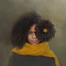 Portrait Of Young Girl With Curly Hair Wearing Yellow Scarf With Black Sunflower In Her Hair