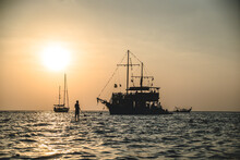 Silhouette Of Man Near Sail Boat And A Ship During Sunset