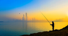 Silhouette Of Man Holding Black Fishing Rod Standing In Front Of Body Of Water During Golden Hours