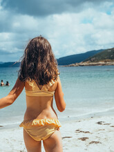 Vertical Shot Of A Back View Of Little Girl In A Bikini On The Beach With The Sea In The Background