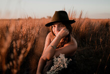Woman Wearing Brown Top And Hat Standing In Field