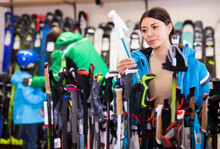Focused Young Female Skier Looking For Fit Ski Poles In Sport Equipment Store