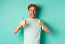 Excited Young Man With Red Hair, Wearing Glasses, Showing Thumbs-up And Agree Or Praise Something, Smiling Amazed And Saying Yes, Standing Over Turquoise Background