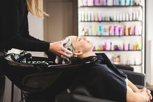 Master Woman Hairdresser Washes Hair Of A Girl With Shampoo Before Styling In A Beauty Salon.