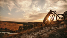 Cyclist With Mountain Bike At Sunset