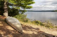 Canoe On A Lake Shoreline During Sunset.