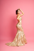 Side View Full-length Portrait Of Attractive, Regal Woman In Long Shining Beige Dress With Train And Lace Or Embroidery, Isolated On Pink Background.