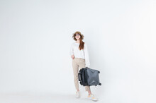 Happy Asian Woman Traveler With Sunglasses And Hat Carrying Baggage Isolated On Grey Background.Happy Tourist Girl Having Cheerful Holiday Trip Carrying Luggage Or Suitcase.