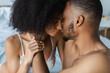 African american man kissing sensual girlfriend in bra on bed.