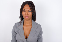Young African American Business Woman With Braids Over White Wall Expressing Disgust, Unwillingness, Disregard Having Tensive Look Frowning Face, Looking Indignant With Something.