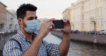 Young Man Traveler Wearing Face Mask Using Phone On Street