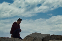 Man In Red Long Sleeve Shirt Sitting On Rock Under White Clouds And Blue Sky In The Mountain