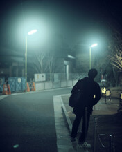 Man With Backpack Standing On Sidewalk During Night Time