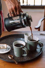 Person Pouring Two Coffee Mugs