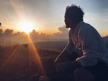 Silhouette Of A Man Sitting During Sunset