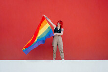 Young Woman Holding Rainbow Flag Standing Against Red Background