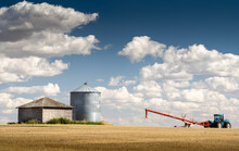 A Farm Tractor And Auger Filling A Grain Silo On A Prairie Wheat Field In Rockyview County Alberta Canada.