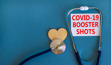Covid-19 Booster Shots Vaccine Symbol. White Card With Words Covid-19 Booster Shots, Beautiful Blue Background, Wooden Heart And Stethoscope. Covid-19 Booster Shots Vaccine Concept.