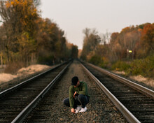 Young Man On Railroad Train Tracks