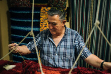 A Craftsman With A Blue Plaid Shirt Working A Loom