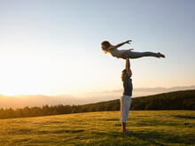 Couple Practicing Acro Yoga Pose On Meadow In Sunrise