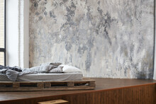 Unfilled Bed Made Of Wooden Blocks With Beige Bedding In The Bedroom Against A Wall With Venetian Stucco. Scandinavian Style