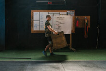 Male Trainer Carrying Wooden Box In Gym