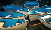 Six Rowing Boats With Bright Blue Inners Moored Up Together.