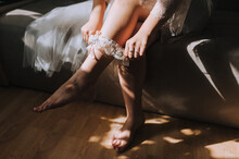 A Beautiful Bride Puts A Garter On Her Leg While Sitting On The Bed In The Morning In The Interior. Wedding Photography.