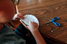 Boy Folding Coffee Filter To Make Paper Snowflake.
