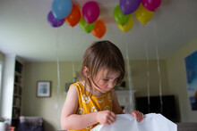 Child Removes Wrapping Paper From Birthday Gift