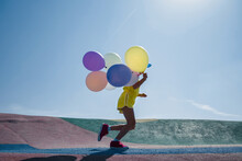 Anonymous Child Running With Colorful Balloons