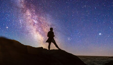 Night Stars Over Woman's Silhouette At The Ocean Water