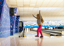 A Little Girl Excited At A Bowling Alley