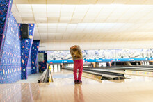 A Little Girl Looking Down A Bowling Alley