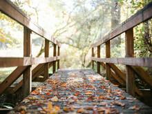 Old Red Wood Bridge Covered In Fallen Leaves