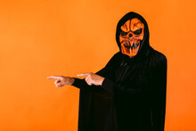 Man Dressed In Latex Pumpkin Mask And Hooded Velvet Cape Points His Fingers To His Left Where There Is Copy Space. Halloween And Days Of The Dead Concept.