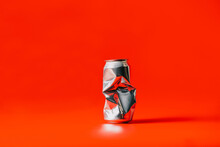 A Crushed Can With Red Background