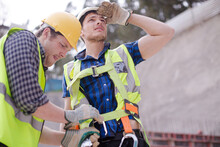 Construction Worker Fastening Coworker's Safety Harness