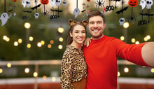 Holiday And People Concept - Happy Smiling Couple In Halloween Costumes Of Devil And Leopard Taking Selfie Over Roof Top Party Background