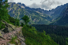 Beautiful Summer Landscape Of High Tatras, Slovakia – Famous Track To Poprad Lake – Stone Footpath Over The Cliff, Lush Forest, Mountains And Clouds On The Sky