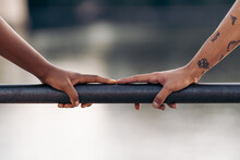 Fingers Of People Of Different Ethnicity Touching Each Other On A Railing