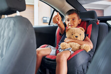 Little Boy With Teddy Bear Is Sitting In The Automobile