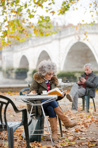Active senior woman reading book, enjoying cake and coffee at autumn park cafe