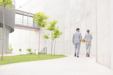 Supervisors Walking On Sidewalk Below Building